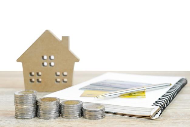 Hausmodell und notizblock mit münzen auf tisch für finanz- und bankkonzept