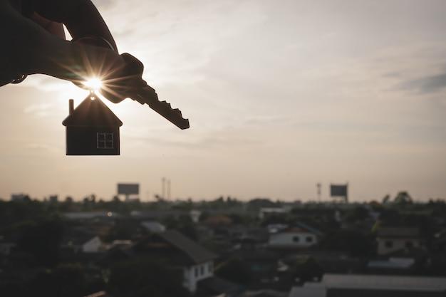 Hausmodell und -schlüssel in der hand des hausversicherungsmakleragenten oder in der verkäuferperson.