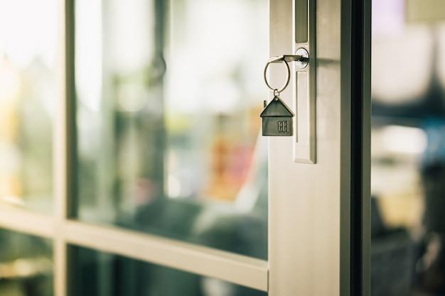 Hausmodell und schlüssel in der haustür.