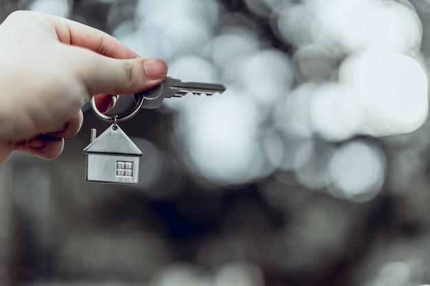 Hausmodell und schlüssel in der hausversicherungsmakleragentenhand