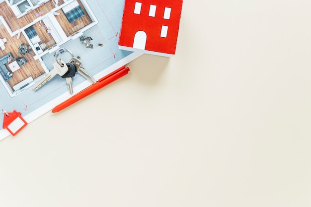 Hausmodell und -schlüssel mit dem plan lokalisiert auf weißem hintergrund