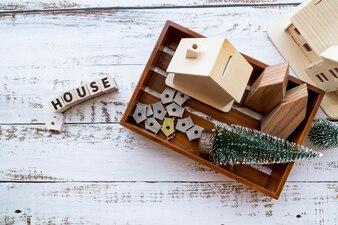 Hausmodell; Vogelhäuschen und Weihnachtsbaum im hölzernen Tablett mit Text auf weißem strukturiertem Hintergrund