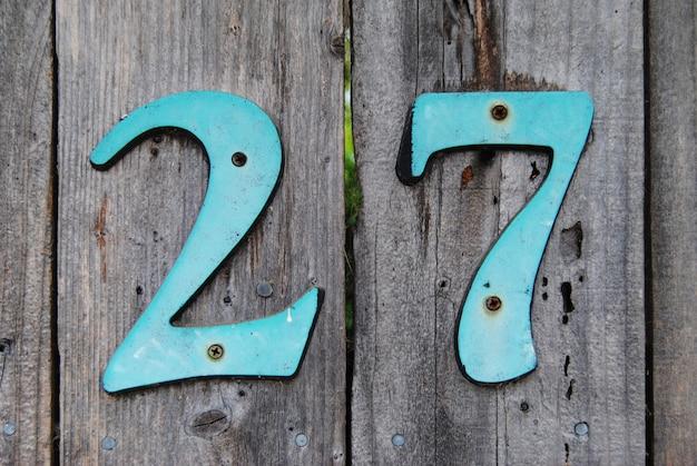 Hausnummer 27 zeichen auf grauem bretterzaun