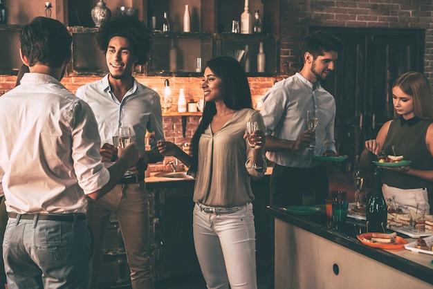 Hausparty mit den nächsten freunden. gruppe fröhlicher junger leute, die eine heimparty mit snacks und getränken genießen, während sie in der küche kommunizieren communicating
