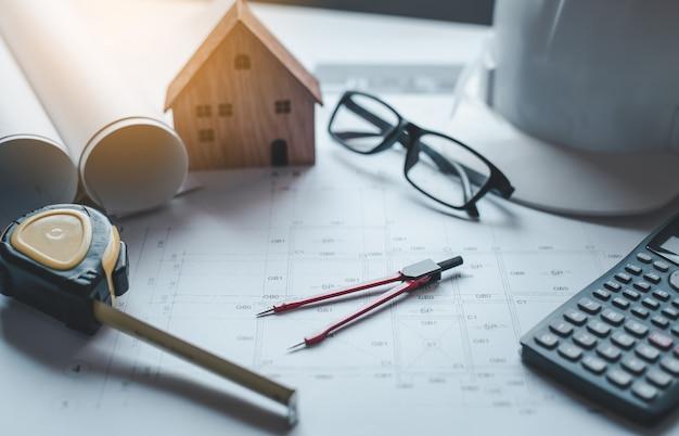 Hausplan auf einem schreibtisch mit arbeitsmitteln