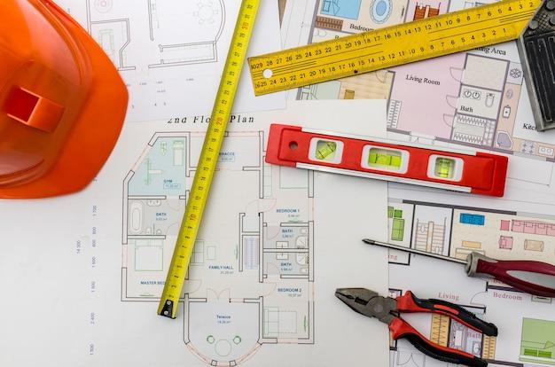 Hausprojektzeichnungen mit helm, maurerwerkzeuge auf holzhintergrund