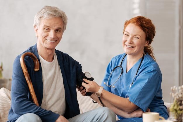 Hausprüfung. fähige, geschickte medizinische mitarbeiterin, die spezielle geräte einsetzt, um eine allgemeine untersuchung durchzuführen, während sie ihre patientin zu hause besucht