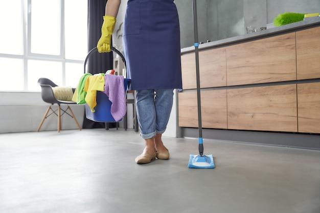Hausputz. frau, die mopp und plastikeimer oder korb mit lappen, reinigungsmitteln und verschiedenen reinigungsmitteln hält, während sie zu hause in der küche steht. hausarbeit, reinigung, housekeeping-konzept