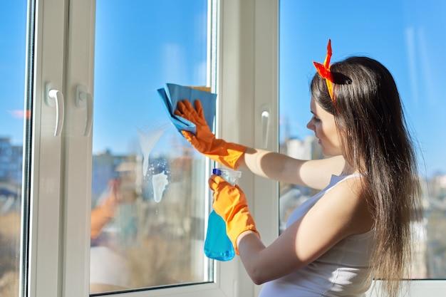 Hausreinigung, junge schöne frau in handschuhen mit waschmittel und lappenwaschfenstern
