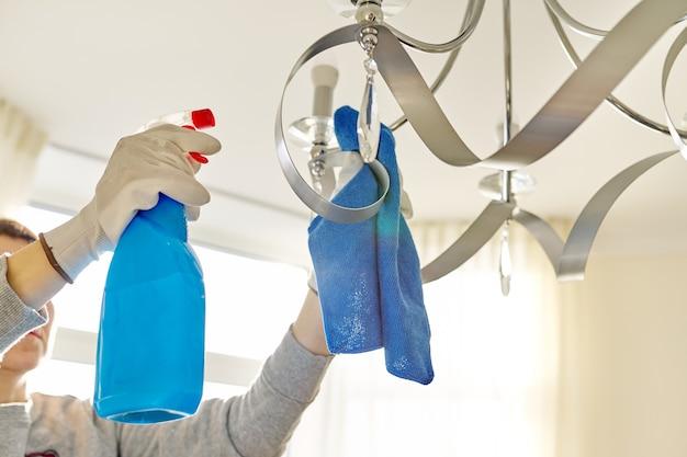Hausreinigung, nahaufnahme der hände mit lappenwaschmittel, reinigungs- und polierlampe, kronleuchter