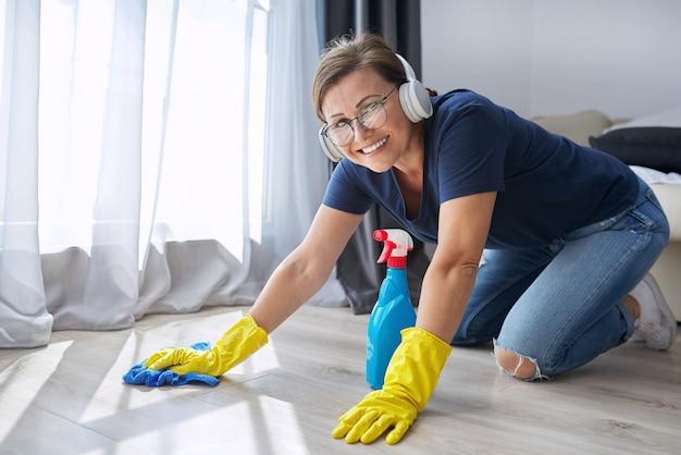 Hausreinigung positiv, frau in kopfhörerhandschuhen mit lappen und reinigungsmittel reinigt den schmutzigen boden, kopierraum. hygiene, reinheit, zuhause, sauberkeitskonzept