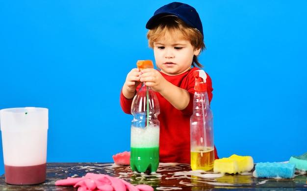 Hausreinigung und haushaltsaufgaben kleiner junge, der mit reinigungsspray-reinigungsmitteln spielt