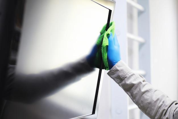 Hausreinigungskonzept. wischen sie staub von oberflächen ab. desinfektionsbehandlung von türgriffen tv elektrisch. sanitäre behandlung zu hause in quarantäne.