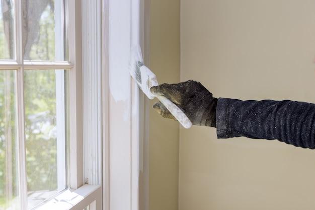 Hausrenovierung im handwerker malt mit einer schicht weißen farbpinsel fensterleisten
