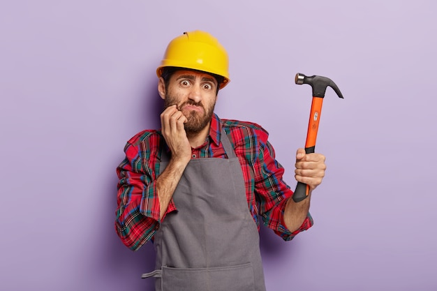 Hausrenovierungskonzept. empörter baumeister hält hammer, repariert