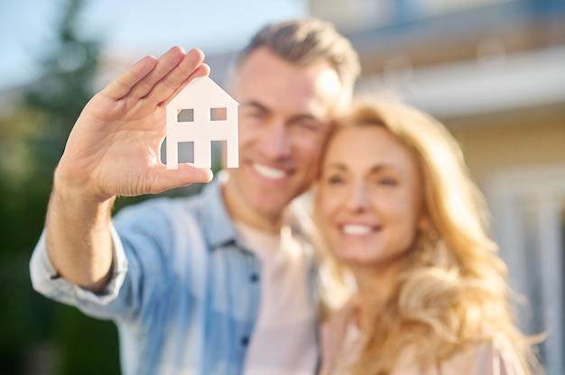 Hausschild in der hand eines mannes, der frau umarmt