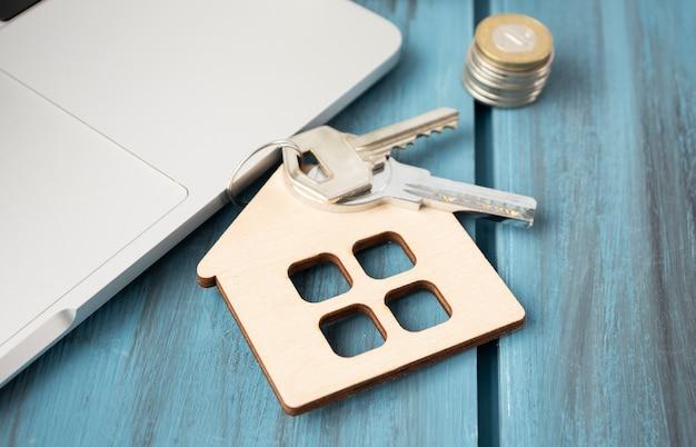 Hausschlüssel am hausförmigen schlüsselbund auf holzdielen