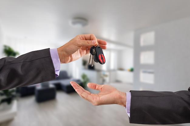 Hausschlüssel am hausförmigen schlüsselbund vor einem neuen zuhause halten