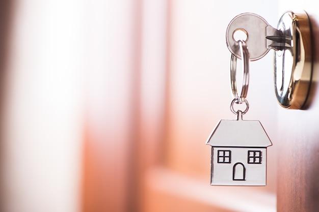 Hausschlüssel an einem hausförmigen silbernen schlüsselring im schloss einer braunen eingangstür