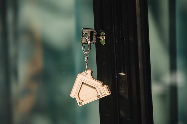 Hausschlüssel an einem hausförmigen silbernen schlüsselring im schloss einer eingangsspiegeltür