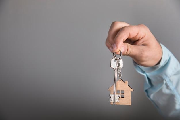 Hausschlüssel an grauer wand halten