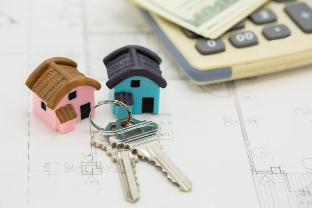 Hausschlüssel auf dem taschenrechner mit dollarscheinen
