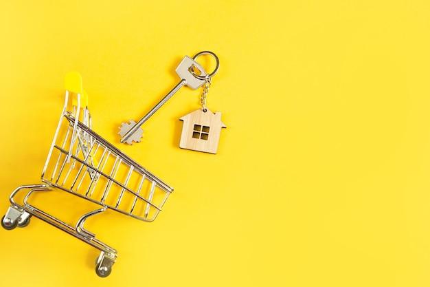 Hausschlüssel auf gelbem hintergrund und einkaufswagen.