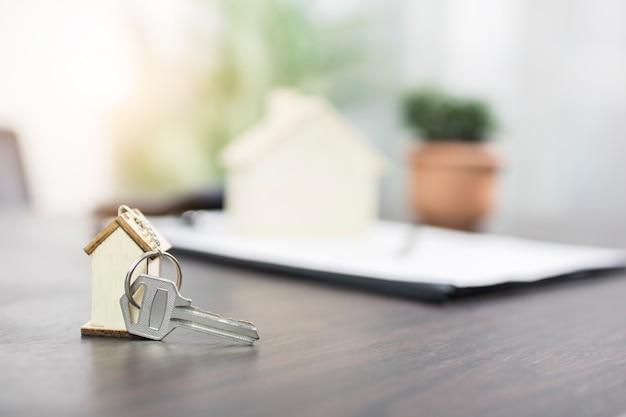 Hausschlüssel auf tabelle mit vertragsformular, haus- oder eigentumswohnungskonzept verkaufend und kaufend