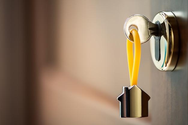 Hausschlüssel in der tür. schließen sie den hausschlüssel auf einem hausförmigen silbernen schlüsselring im schloss einer braunen eingangstür mit kopierraum