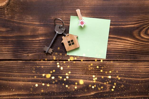 Hausschlüssel mit einem schlüsselbund in der form eines häuschens auf einem hölzernen hintergrund