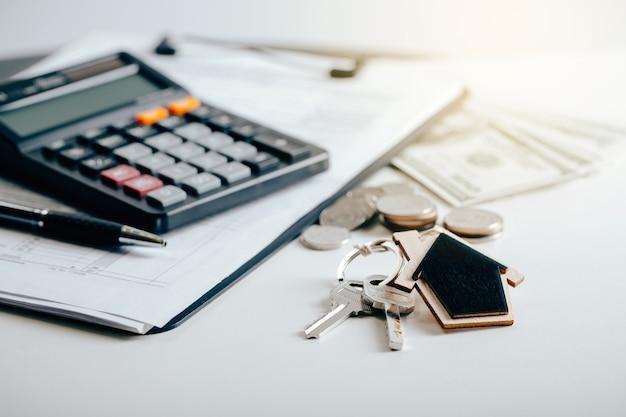 Hausschlüssel mit immobilienmakler und kunde, die über einen vertrag zum kauf eines hauses diskutieren. versicherungs- oder darlehensimmobilienkonzept