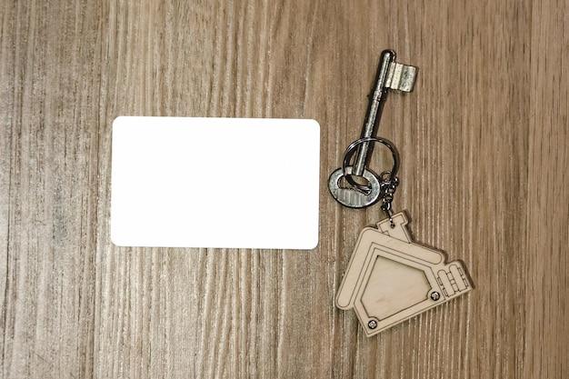 Hausschlüssel mit modell der kreditkarte auf holztisch