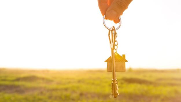 Hausschlüssel mit schlüsselanhänger in der hand. hintergrund von himmel, sonnenlicht und feld. traum vom eigenheim, bau eines landhauses im grünen, planung und projektierung, bauernhof, umzug in ein neues zuhause, unterkunft. platz kopieren