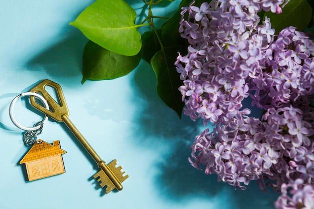 Hausschlüssel mit schlüsselbund auf blauem frühlingshintergrund und lila zweigen. sommerferienhaus, ferienhaus auf dem land buchen, in ein neues zuhause umziehen, hypothek, miete und kauf von immobilien. tourismus