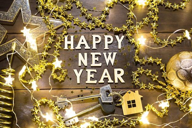 Hausschlüssel mit schlüsselbundhaus auf festlichem hintergrund mit pailletten, sternen, lichtern der girlanden. frohes neues jahr - holzbriefe, grüße, grußkarte. kauf, bau, umzug, hypothek