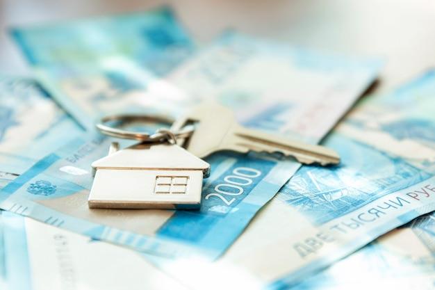 Hausschlüssel sind auf den rechnungen. russische rubel. hypotheken, kredite und spareinlagen. nahaufnahme.