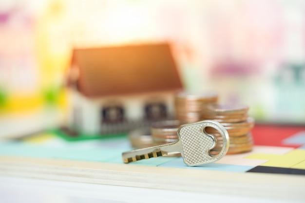 Hausschlüssel und hausmodell als kulisse. konzept für immobilienleiter, hypotheken und immobilieninvestitionen.