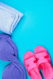 Hausschuhe, badeanzug, handtuch auf blauem pastellhintergrund. ruhe dich aus, reise. draufsicht. speicherplatz kopieren. flach liegen.