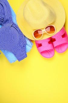 Hausschuhe, badeanzugbikini, handtuch, hut und sonnenbrille auf pastellgelbem hintergrund.