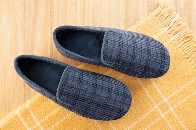 Hausschuhe für männer und wolldecke auf dem tisch. zuhause entspannen im winterkonzept
