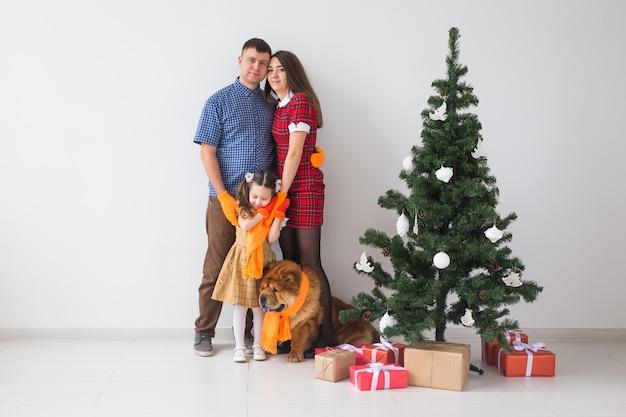Haustier, feiertage und festliches konzept - familie mit hund stehen nahe weihnachtsbaum.