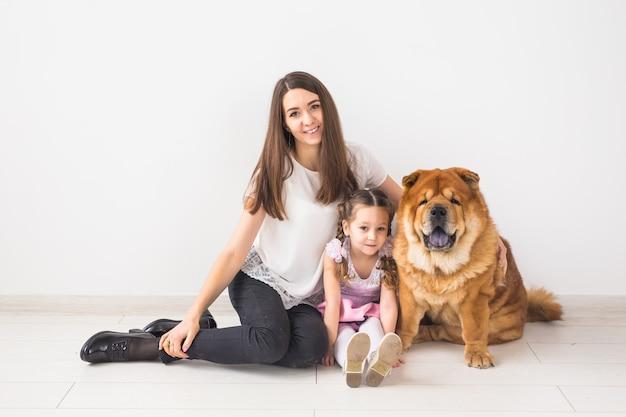 Haustier, kinder und familienkonzept - kleines mädchen und ihre mutter, die chow-chow-hund über weiß umarmen