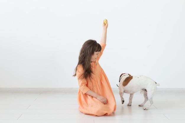 Haustier-, kinder- und hundekonzept - kleines mädchen im kleid, das mit welpen spielt