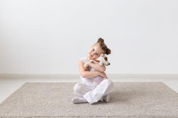 Haustier, kindheit und tierkonzept - porträt des kleinen kindermädchens, das mit welpen jack russell terrier auf dem boden sitzt