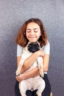 Haustier liebe. das lockige teenager-mädchen umarmt ihren traurigen mops mit liebe