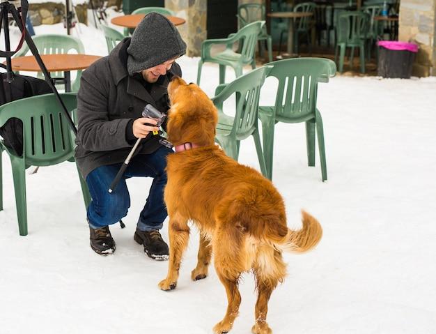Haustierbesitzer, hund und menschen-konzept - junge lächelnde kaukasische mann und hund im freien im winter.