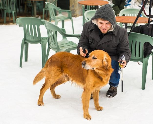 Haustierbesitzer, hund und menschen-konzept - junger lächelnder kaukasischer mann und hund im freien im winter.