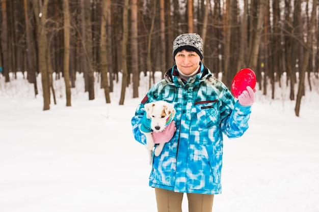 Haustierbesitzer und winterkonzept - frau mittleren alters, die mit ihrem jack russell terrier-hund im schnee spielt
