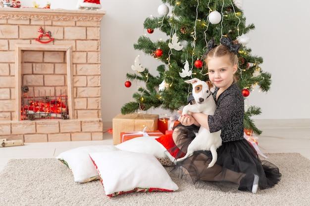 Haustiere, feiertage und weihnachtskonzept - kindermädchen, das mit welpen jack russell terrier nahe weihnachtsbaum spielt.