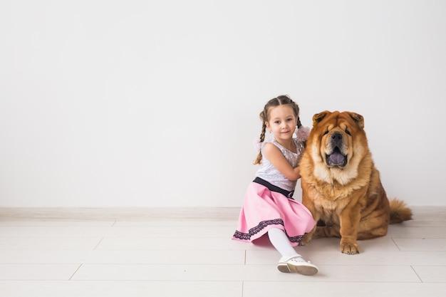 Haustiere, kinder und freundschaftskonzept - kleines mädchen, das ihren hund chow-chow über leerraum umarmt
